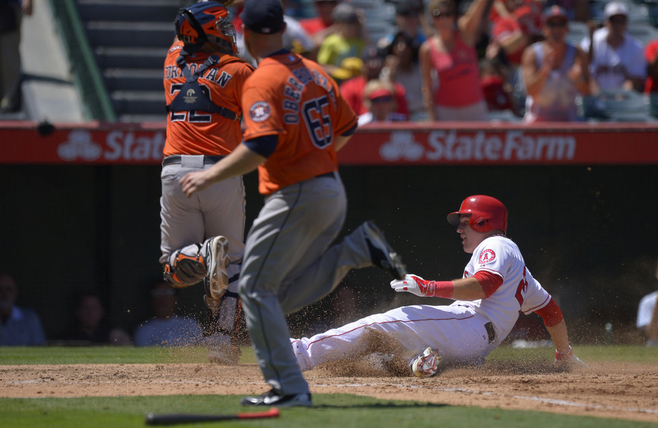 Photo - Los Angeles Angels' Mike Trout, right, scores on a single by Mark Trumbo as Houston Astros catcher Carlos Corporan, left, takes a high throw and relief pitcher Brett Oberholtzer backs him up during the third inning of their baseball game on Sunday, Aug. 18, 2013, in Anaheim, Calif. (AP Photo/Mark J. Terrill)