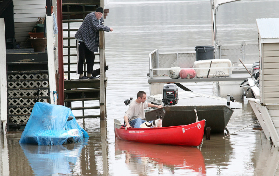 Photo - Residents deal with the high water Tuesday afternoon, April 23, 2013 in Grafton, Ill. More rain on Tuesday was the last thing flood fighters across the Midwest wanted to see, adding more water to swollen rivers that are now expected to remain high into next month. (AP Photo/Belleville News-Democrat, Derik Holtmann)