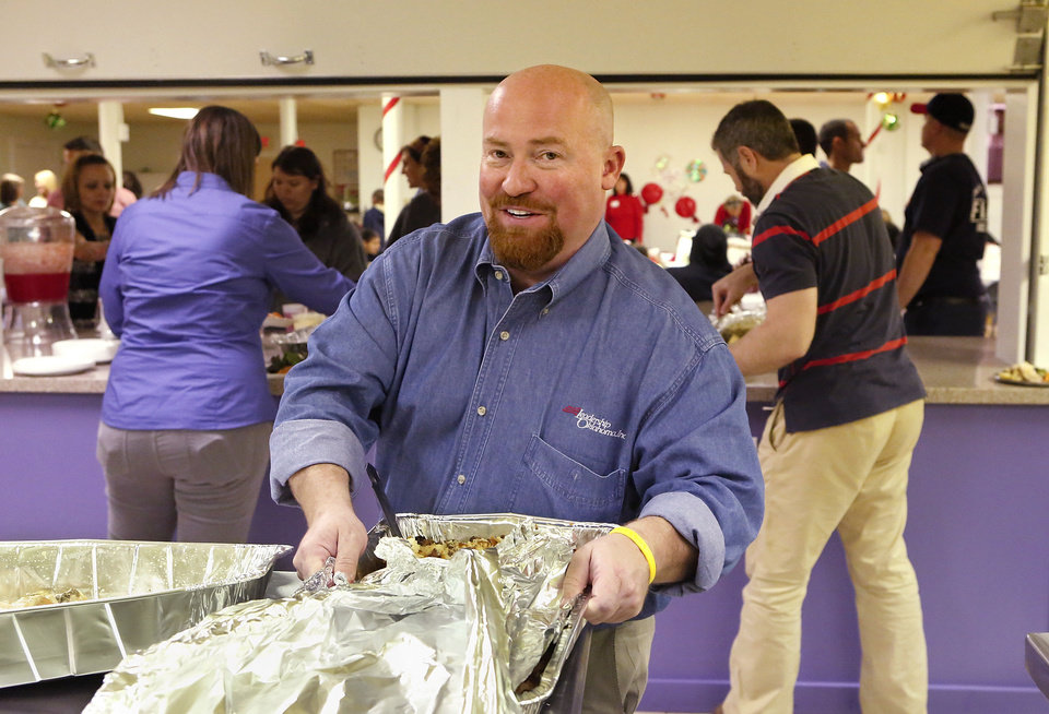 Photo - Oklahoma Rep. Joe Dorman helps serve lunch at  Positive Tomorrows.