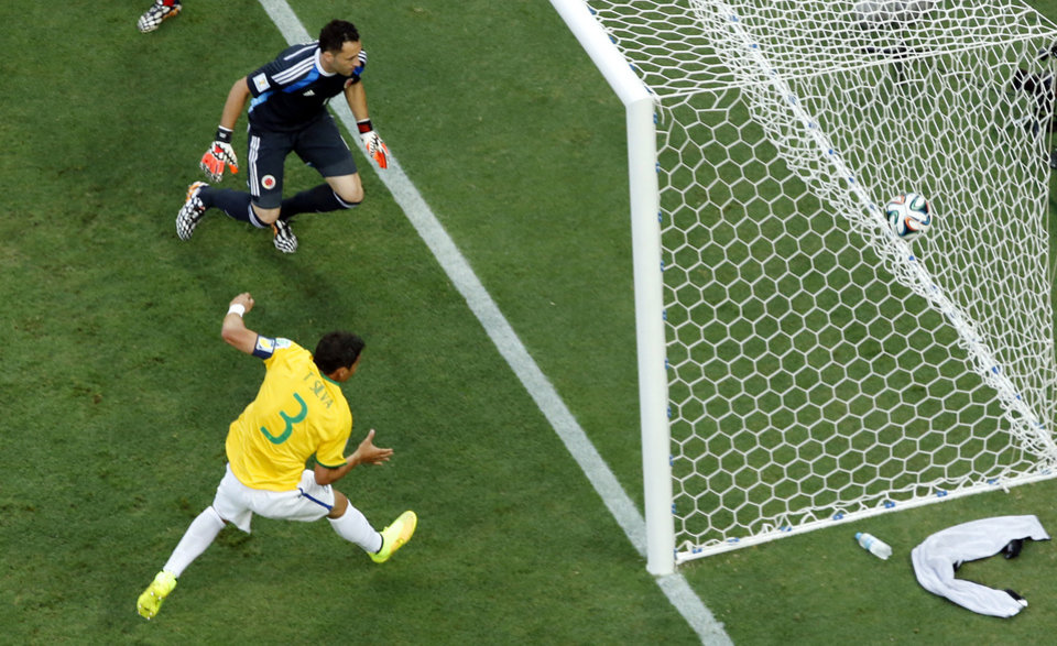 Photo - Brazil's Thiago Silva, bottom, scores his side's first goal during the World Cup quarterfinal soccer match between Brazil and Colombia at the Arena Castelao in Fortaleza, Brazil, Friday, July 4, 2014. (AP Photo/Fabrizio Bensch, pool)