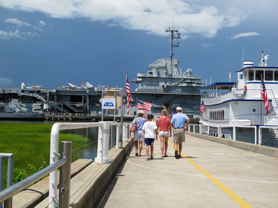 Photo - FILE - In this Aug. 7, 2012 file photo, visitors walk toward the USS Yorktown at the Patriots Point Naval and Maritime Museum in Mount Pleasant, S.C. Tourism is an $18 billion industry in South Carolina and a new season is gearing up the week of February 9, 2014 with the Governor's Conference on Tourism and Travel on Hilton Head Island, the Southeastern Wildlife Exposition in Charleston and other events. (AP Photo/Bruce Smith, File)