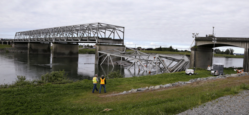 Photo - Workers walk past the collapsed portion of the Interstate 5 bridge at the Skagit River Friday, May 24, 2013, in Mount Vernon, Wash. A truck carrying an oversize load struck the four-lane bridge on the major thoroughfare between Seattle and Canada, sending a section of the span and two vehicles into the Skagit River below Thursday evening. All three occupants suffered only minor injuries. At an overnight news conference, Washington State Patrol Chief John Batiste blamed the collapse on a tractor-trailer carrying a tall load that hit an upper part of the span. (AP Photo/Elaine Thompson)