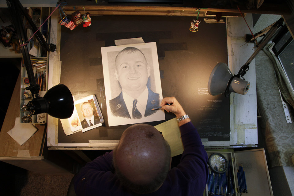 In this Thursday, Oct. 4, 2012 photo, artist Michael Reagan works on a portrait of Joseph A. Weems, who died after being after being hit by a train while riding his bicycle near the Ramstein Air Base in Germany as he served in the U.S. Air Force at his home in Edmonds, Wash. Since starting the Fallen Heros Project in 2004, Reagan has drawn more than 3,000 portraits and given them free-of-charge to families of fallen soldiers. (AP Photo/Ted S. Warren)