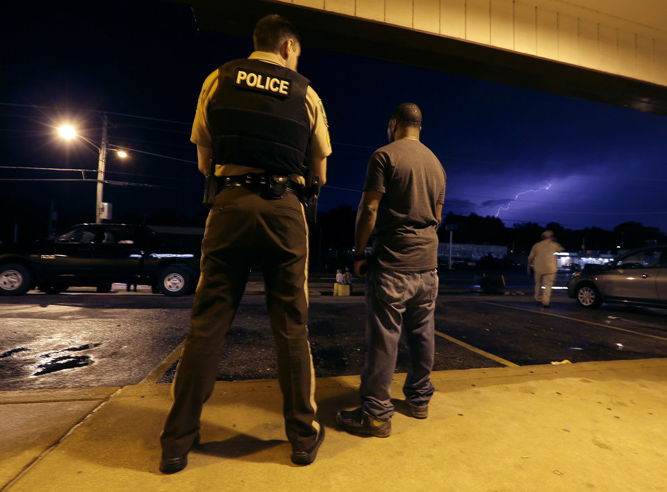 Photo - St. Louis County Police Sgt. Colby Dolly and Charles Mayo talk while waiting out a thunderstorm during a protest of the shooting of Michael Brown Wednesday, Aug. 20, 2014, in Ferguson, Mo. Brown's shooting in the middle of a street Aug 9, by a Ferguson policeman has sparked more than week of protests, riots and looting in the St. Louis suburb. (AP Photo/Charlie Riedel)
