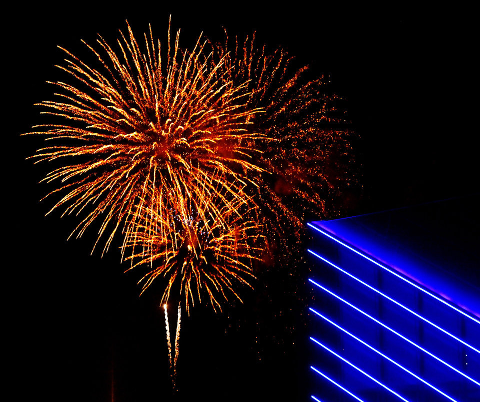 The blue lights of the Devon Boathouse frame a burst of colorful fireworks. Boat Parade and fireworks  on the Oklahoma River Friday night,   Nov. 25, 2011.  Photo by Jim Beckel, The Oklahoman