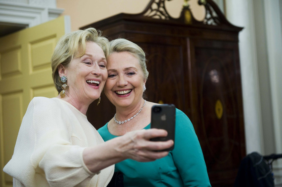 Photo - Actress Meryl Streep uses her iPhone to get a photo of her and Secretary of State Hillary Rodham Clinton following the State Department Dinner for the Kennedy Center Honors gala Saturday, Dec. 1, 2012 at the State Department in Washington. (AP Photo/Kevin Wolf)