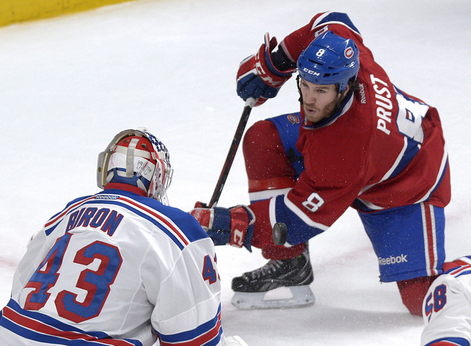 Photo - Montreal Canadiens' Brandon Prust, right, takes a shot at New York Rangers goaltender Martin Biron during the first period  of an NHL hockey game in Montreal, Saturday, Feb. 23, 2013. (AP Photo/The Canadian Press, Graham Hughes)