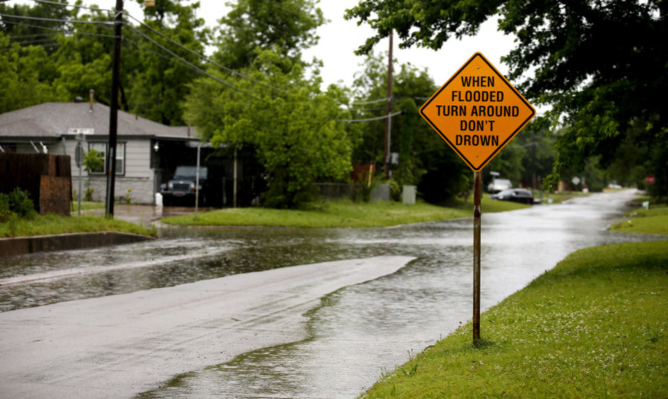 Photo - High water is pictured near NW 34th and Hammond in Warr Acres, Okla., after severe storms moved through the metro area, Saturday, May 18, 2019 Photo by Sarah Phipps, The Oklahoman