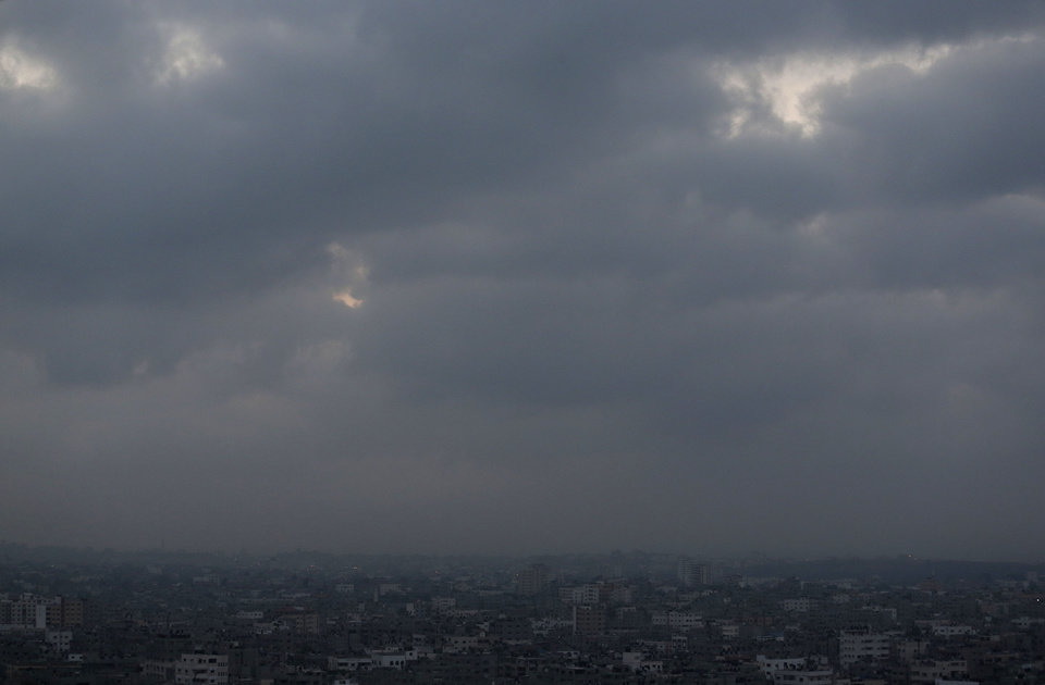 Photo - Clouds hover over Gaza city, early Monday, July 28, 2014. Monday marked the beginning of the three-day Eid al-Fitr holiday, which caps the Muslim fasting month of Ramadan. Muslims usually start the day by visiting cemeteries, to pay their respects to the dead, and then exchange family visits. (AP Photo/Lefteris Pitarakis)