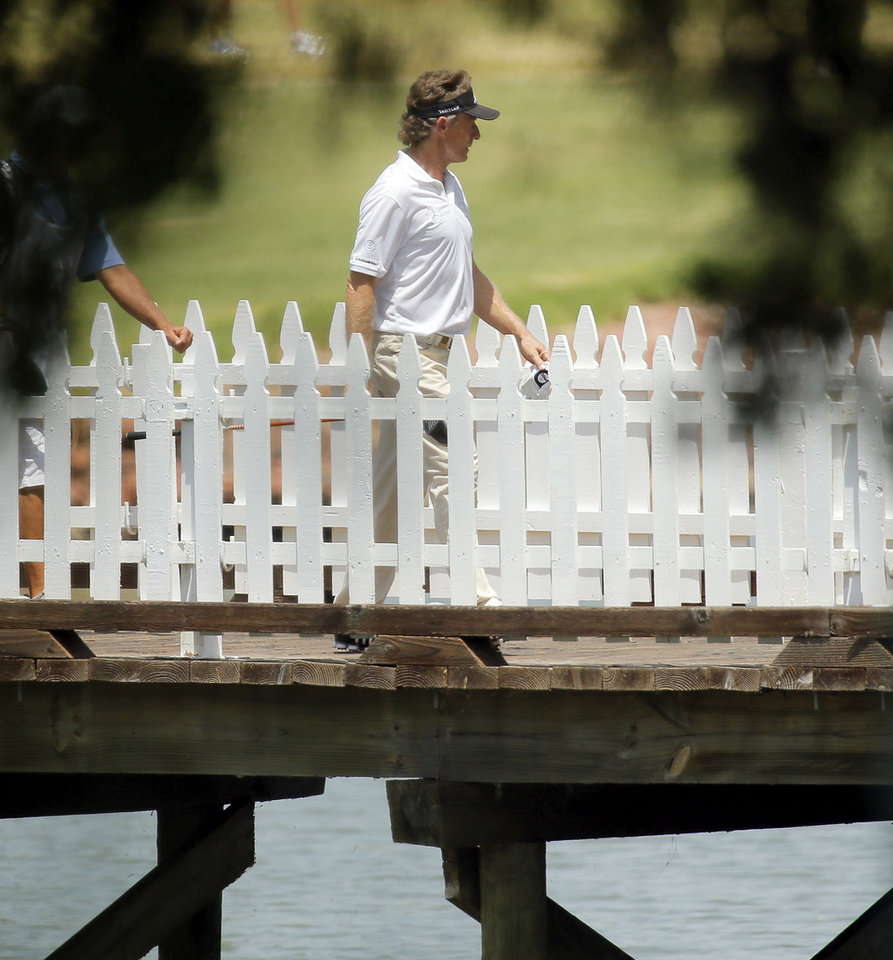 Photo - Bernhard Langer crosses a bridge on No. 9 during the third round of the U.S. Senior Open golf tournament at Oak Tree National in Edmond, Okla., Saturday, July 12, 2014. Photo by Nate Billings, The Oklahoman