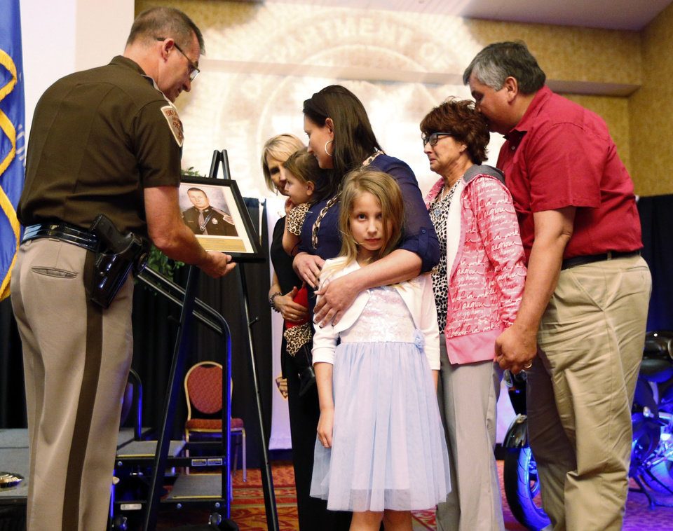 Photo -  Trooper Nicholas Dees' family gathers around the unveiling of a plaque Wednesday as Dees is honored during the Trooper of the Year Awards Norman. Family members left to right are Sandra Smith Rudisill, Dees' mother-in-law, daughters Piper, 2, and Claire, 8, his widow, Brandi, and the trooper's mother and step-father, Shelly and Mike Russell. Patrol Chief Col. Ricky Adams is at left. Photo by Steve Sisney, The Oklahoman   STEVE SISNEY -  THE OKLAHOMAN