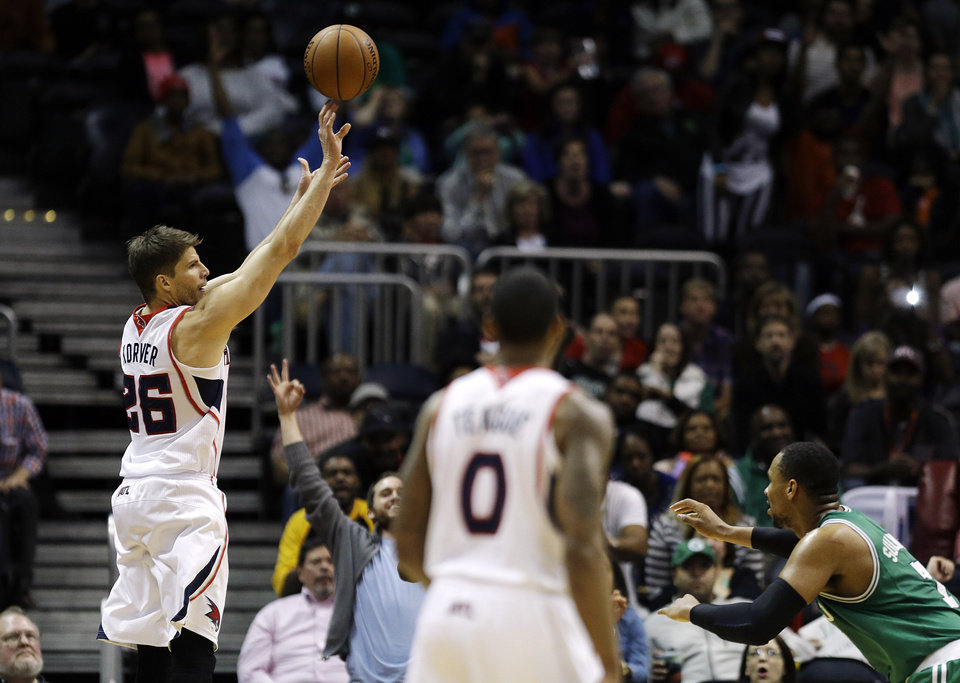 Photo - Atlanta Hawks' Kyle Korver, left, scores a 3-pointer in front of Boston Celtics' Jared Sullinger, right, late in the fourth quarter of an NBA basketball game, Wednesday, April 9, 2014, in Atlanta. The Hawks won 105-97. (AP Photo/David Goldman)