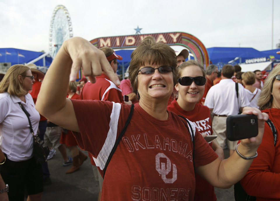 Photo -   An Oklahoma fan gives an upside down horns sign as the Texas team arrives for their NCAA college football game at the Cotton Bowl Saturday, Oct. 13, 2012, in Dallas. (AP Photo/Michael Mulvey)