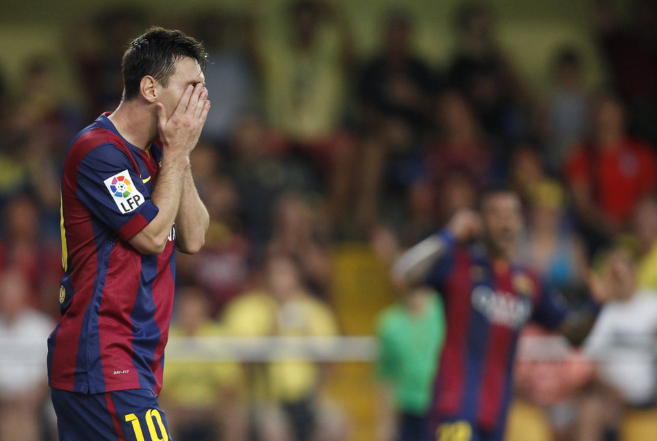 Photo - Barcelona's Lionel Messi, from Argentina, covers his face after failing to score against Villarreal during a Spanish La Liga soccer match at the Madrigal stadium in Villarreal, Spain, on Sunday, Aug 31, 2014.(AP Photo/Alberto Saiz)