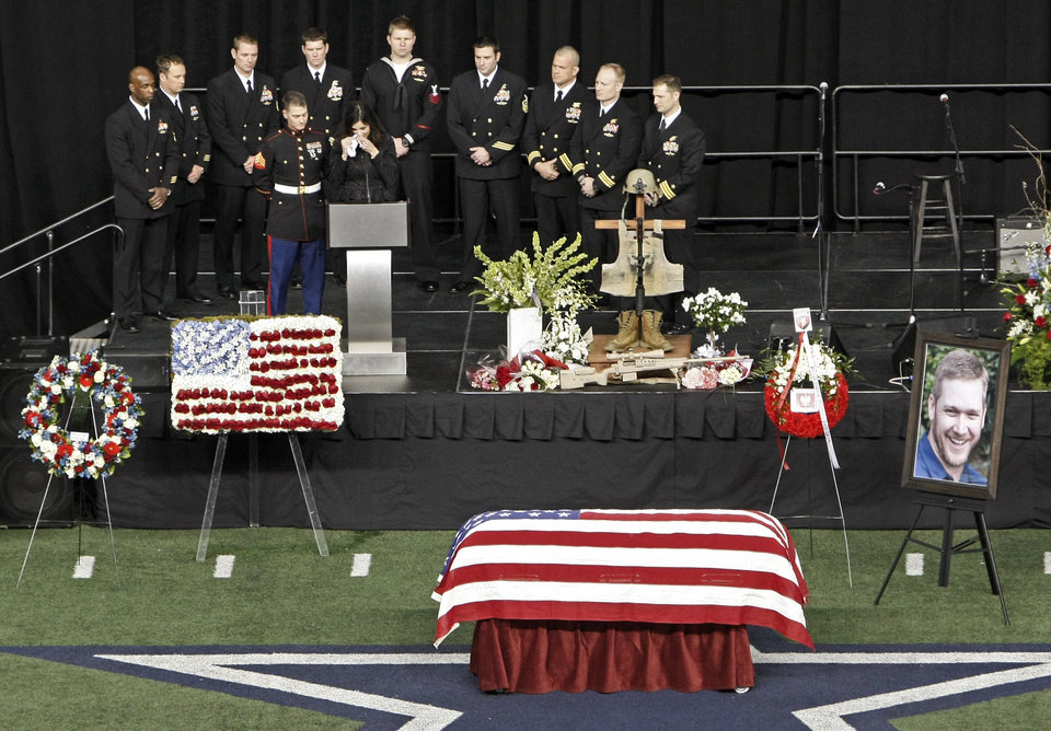 Christopher Kyle's wife, Taya, wipes tears away while memorializing her husband during a memorial service at Cowboys Stadium, Monday, Feb. 11, 2013, in Arlington, Texas. Thousands attended the public memorial service for Kyle, the former Navy SEAL sniper who was shot to death at a Texas shooting range. (AP Photo/Brandon Wade)