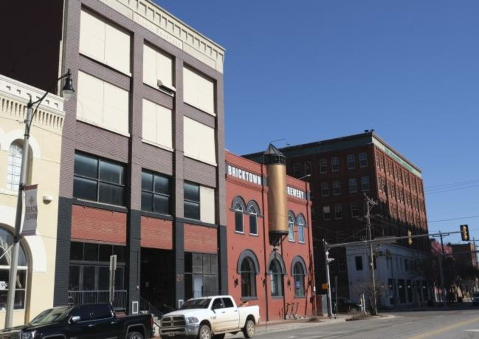 Photo -  The four-story former Henry Hudson's is being converted into a pizzeria by the owners of the neighboring Bricktown Brewery. The former Spaghetti Warehouse, far right, has been empty for four years and awaits a tenant. [DOUG HOKE/THE OKLAHOMAN]