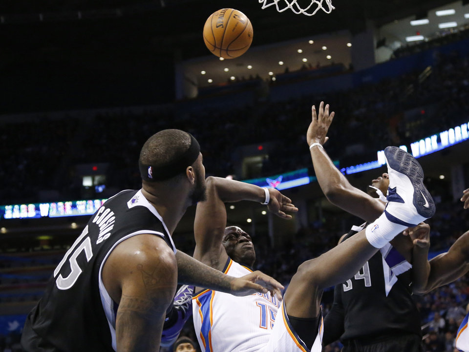 Photo - Oklahoma City Thunder guard Reggie Jackson (15) loses the ball and falls after being fouled by Sacramento Kings center DeMarcus Cousins (15) in the third quarter of an NBA basketball game in Oklahoma City, Sunday, Jan. 19, 2014. Oklahoma City won 108-93. (AP Photo/Sue Ogrocki)