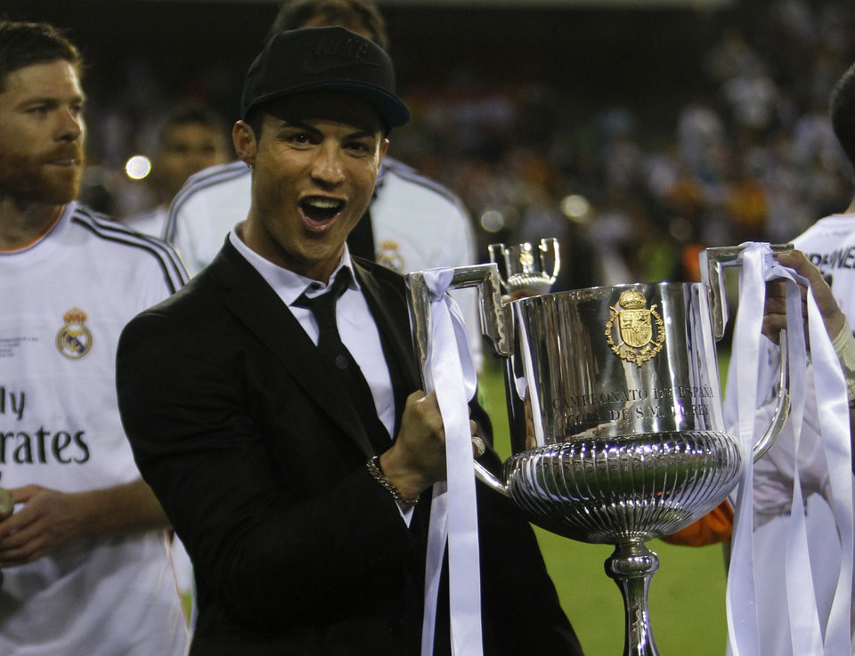 Photo - Real's Cristiano Ronaldo holds the trophy after Real Madrid won the final of the Copa del Rey between FC Barcelona and Real Madrid at the Mestalla stadium in Valencia, Spain, Wednesday, April 16, 2014. Ronaldo was injured and didn't play. (AP Photo/Alberto Saiz)