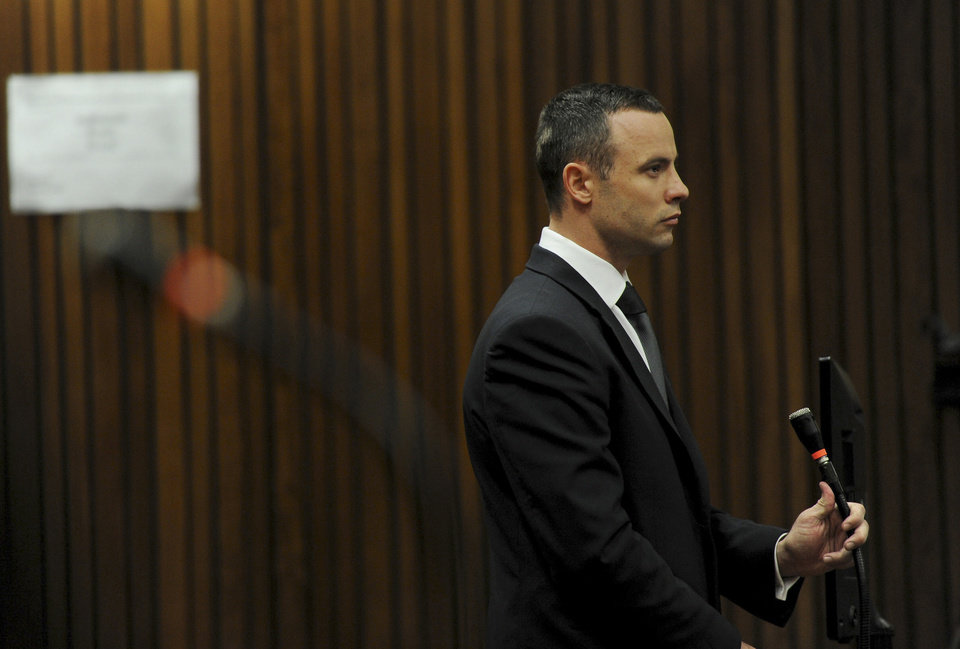 Photo - Oscar Pistorius stands in the dock at the high court in Pretoria, South Africa, Wednesday, May 14, 2014. The judge overseeing the murder trial of Pistorius on Wednesday ordered the double-amputee athlete to undergo psychiatric tests, meaning that the trial proceedings will be delayed. The court adjourned until May 21, 2014. (AP Photo/Werner Beukes, Pool)