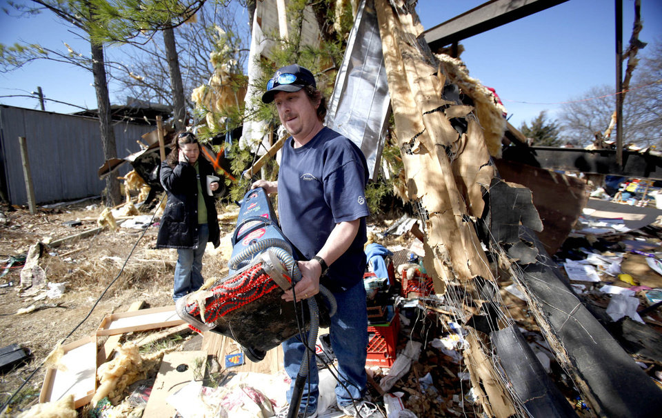 Photo - Thor Clemens and his wife, Christian, clean up tornado damage, Thursday, Feb. 12, 2009, in Lone Grove, Okla. PHOTO BY SARAH PHIPPS, THE OKLAHOMAN