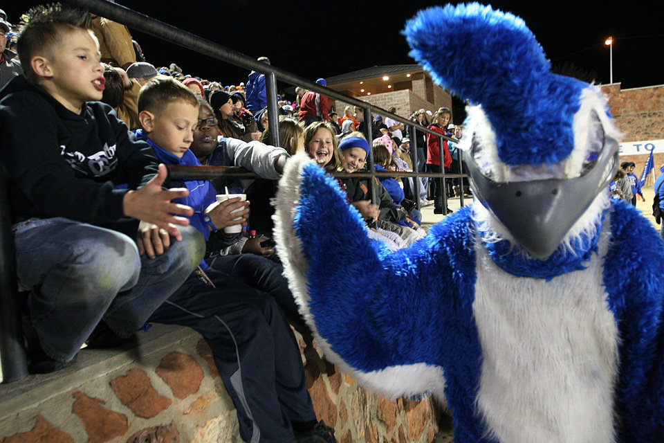 Photo - Dakota Johnson, The Guthrie Bluejay, high-fives children in the stands  during a high school football game between Guthrie and East Central at The Rock in Guthrie, Friday, Nov. 18, 2011.  Photo by Garett Fisbeck, The Oklahoman