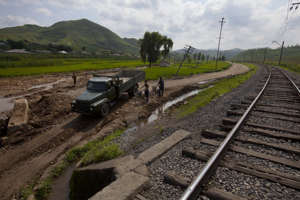 In this Monday, Aug 13, 2012 photo, a North Korean military truck and men on bicycles try to pass through a road, washed out during July 2012 flooding, in Songchon County, North Korea. Twin typhoons are renewing fears of a humanitarian crisis in North Korea, where poor drainage, widespread deforestation and fragile infrastructure can turn even a routine rainstorm into a catastrophic flood. (AP Photo/David Guttenfelder)
