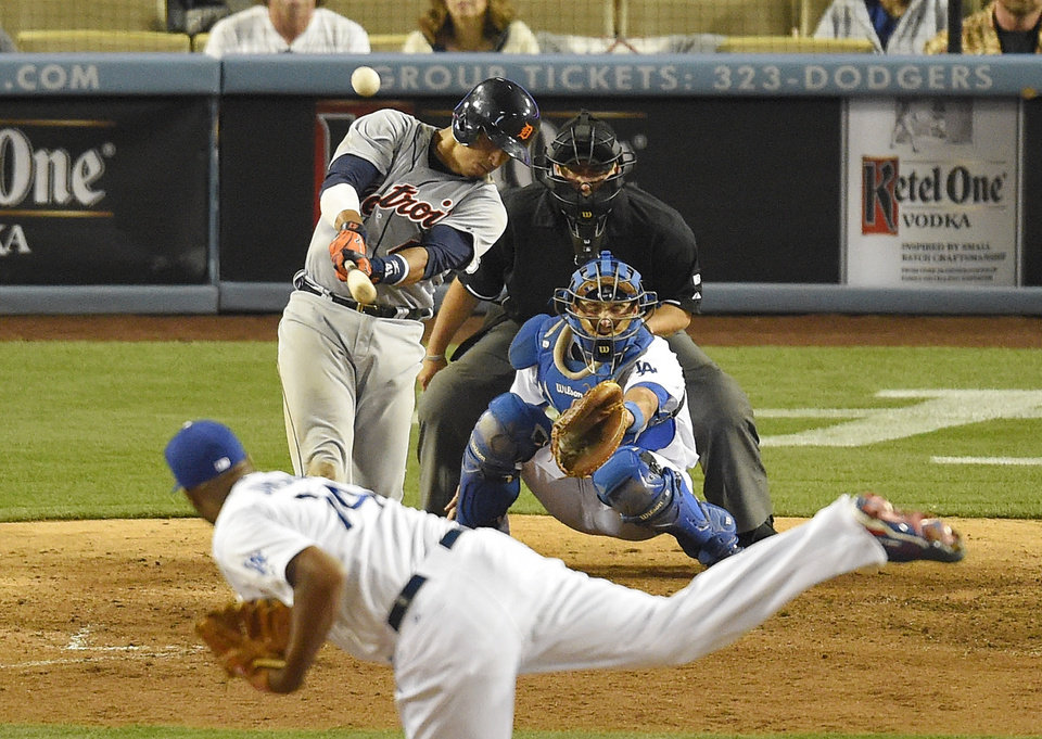 Photo - Detroit Tigers' Victor Martinez, left, hits a solo home run as Los Angeles Dodgers relief pitcher Kenley Jansen, below, pitches and catcher Drew Butera catches during the 10th inning of a baseball game, Wednesday, April 9, 2014, in Los Angeles. (AP Photo/Mark J. Terrill)