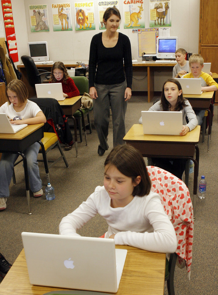 Photo - Fourth grade teacher Carrie Alexander oversees her students working on laptops in her class. Howe Public Schools is using cutting edge technology such as iPods and computers to create podcasts, virtual field trips and help students catch up on homework, Tuesday, February 12, 2008. BY DAVID MCDANIEL, THE OKLAHOMAN    ORG XMIT: KOD