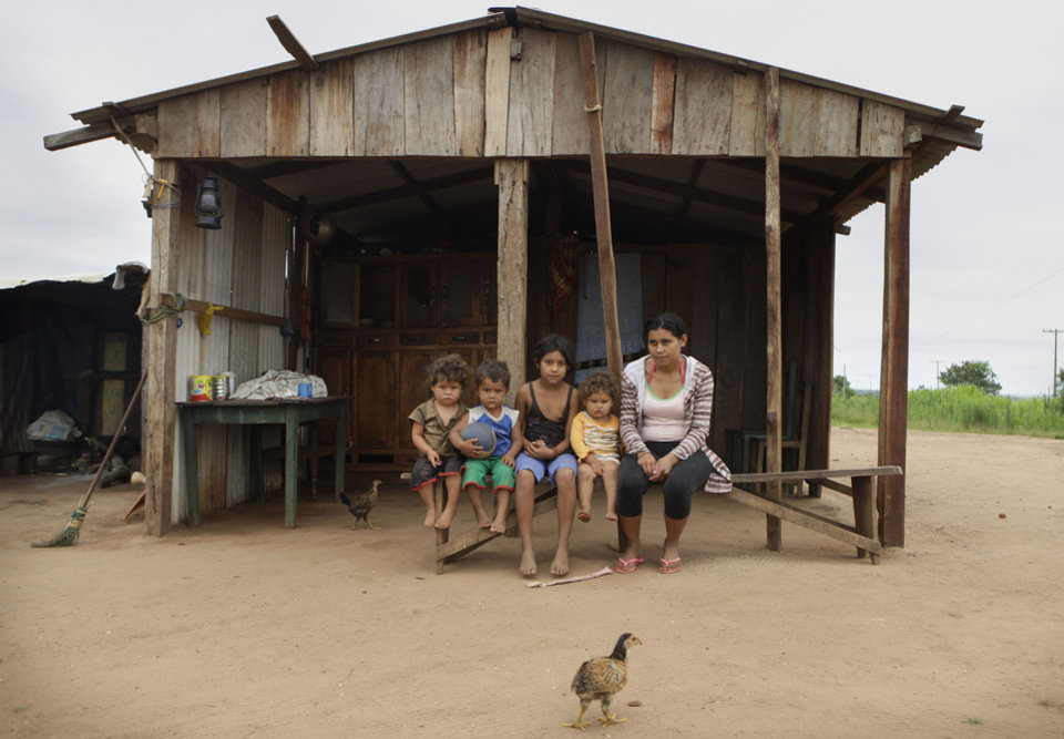 In this Nov. 14, 2012 photo, five of 11 children from the Martinez family pose for a portrait outside their home in the Yvy Pyta settlement near Curuguaty, Paraguay. In Curuguaty, negotiations between farmers occupying a rich politician's land ended with a barrage of bullets that killed 11 farmers and 6 police officers. The underlying dispute that set up the June 15 clash was decades in the making. The area's poor residents have long alleged that the land was effectively stolen from the state by Sen. Blas Riquelme, a leader of the Colorado Party that backed dictator Alfredo Stroessner from 1954 to 1989, and has dominated the nation's politics ever since. (AP Photo/Jorge Saenz)
