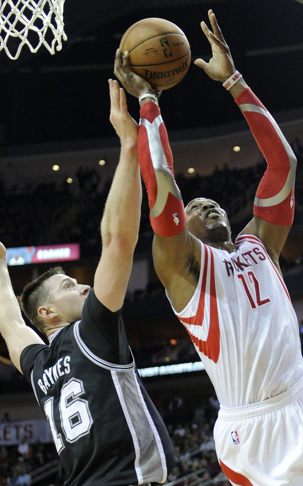 Photo - San Antonio Spurs' Aron Baynes (16) tries to block a shot by Houston Rockets' Dwight Howard (12) in the first half of an NBA basketball game Monday, April 14, 2014, in Houston. (AP Photo/Pat Sullivan)