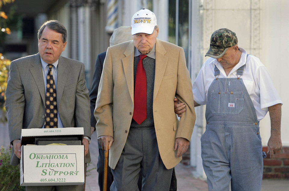 Photo - Former state legislator Gene Stipe, center, arrives with his entourage at the federal courthouse in Muskogee, Okla., for a mental competency hearing Tuesday Oct. 28, 2008. The hearing could determine whether Stipe will face a probation revocation hearing related to felony convictions involving a 1998 campaign fraud scheme. (AP Photo/Tulsa World, Michael Wyke) ORG XMIT: OKTUL101