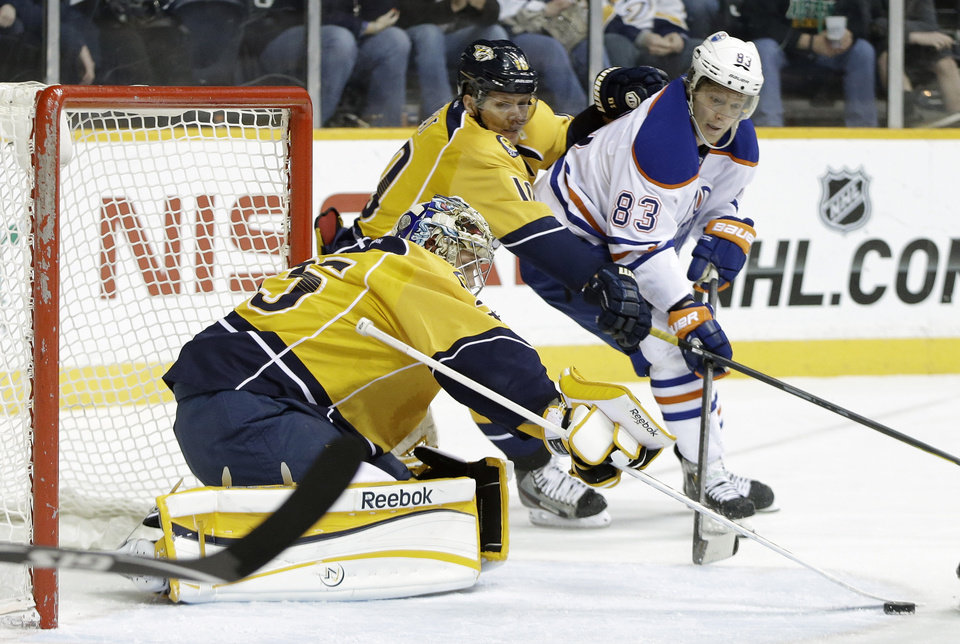 Photo - Nashville Predators goalie Pekka Rinne (35), of Finland, blocks a shot as left wing Martin Erat (10), of the Czech Republic, and Edmonton Oilers right wing Ales Hemsky (83), of the Czech Republic, chase after the rebound in the first period of an NHL hockey game on Monday, March 25, 2013, in Nashville, Tenn. (AP Photo/Mark Humphrey)
