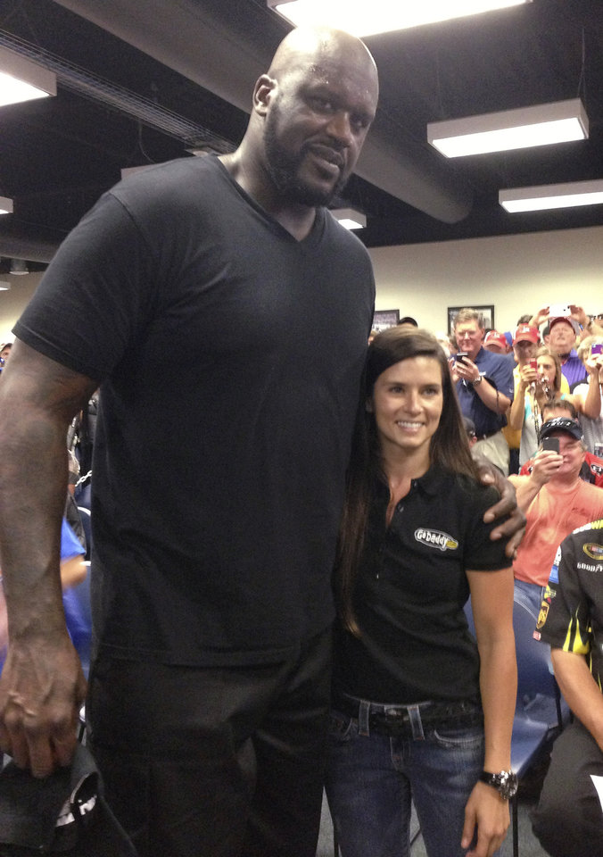 Photo - Former NBA star Shaquille O'Neal, left, and Danica Patrick pose for photos at the drivers' meeting prior to the NASCAR Sprint Cup auto race at Daytona International Speedway, Saturday, July 6, 2013, in Daytona Beach, Fla. (AP Photo/Jenna Fryer)
