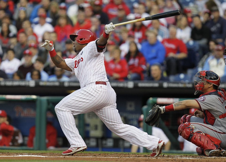 Photo - Philadelphia Phillies' Marlon Byrd, left, follows through on a home run in the first inning of a baseball game against the Washington Nationals, Friday, May 2, 2014, in Philadelphia. (AP Photo/Laurence Kesterson)