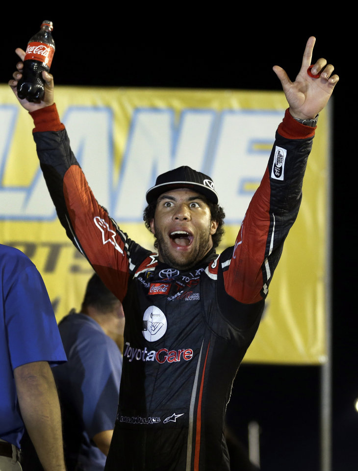 Photo - Darrell Wallace Jr. celebrates after winning the NASCAR Truck Series auto race at Gateway Motorsports Park on Saturday, June 14, 2014, in Madison, Ill. (AP Photo/Jeff Roberson)