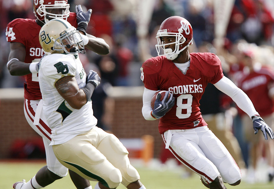 Photo - Oklahoma's Brandon Caleb (8) looks for more running room past Baylor's Jeremy Williams (4) on a reception during the first half of the college football game between the University of Oklahoma Sooners (OU) and the Baylor University Bears at Gaylord Family-Oklahoma Memorial Stadium on Saturday, Oct. 10, 2009, in Norman, Okla. 