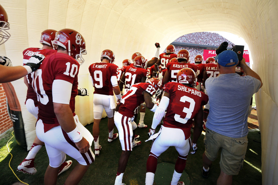 Photo - Oklahoma's Blake Bell (10) and Trevor Knight (9) enter the field through an inflated tunnel during for the college football game where the University of Oklahoma Sooners (OU) play the University of Louisiana Monroe Warhawks at Gaylord Family-Oklahoma Memorial Stadium in Norman, Okla., on Saturday, Aug. 31, 2013. Photo by Steve Sisney, The Oklahoman