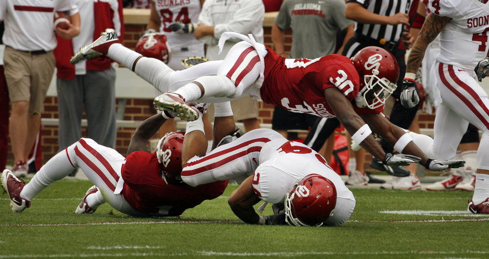 Javon Harris (30) flies over the tackle of Brennan Clay (24) by Tony Jefferson (bottom) during the University of Oklahoma (OU) football team's annual Red and White Game at Gaylord Family/Oklahoma Memorial Stadium on Saturday, April 14, 2012, in Norman, Okla.  Photo by Steve Sisney, The Oklahoman