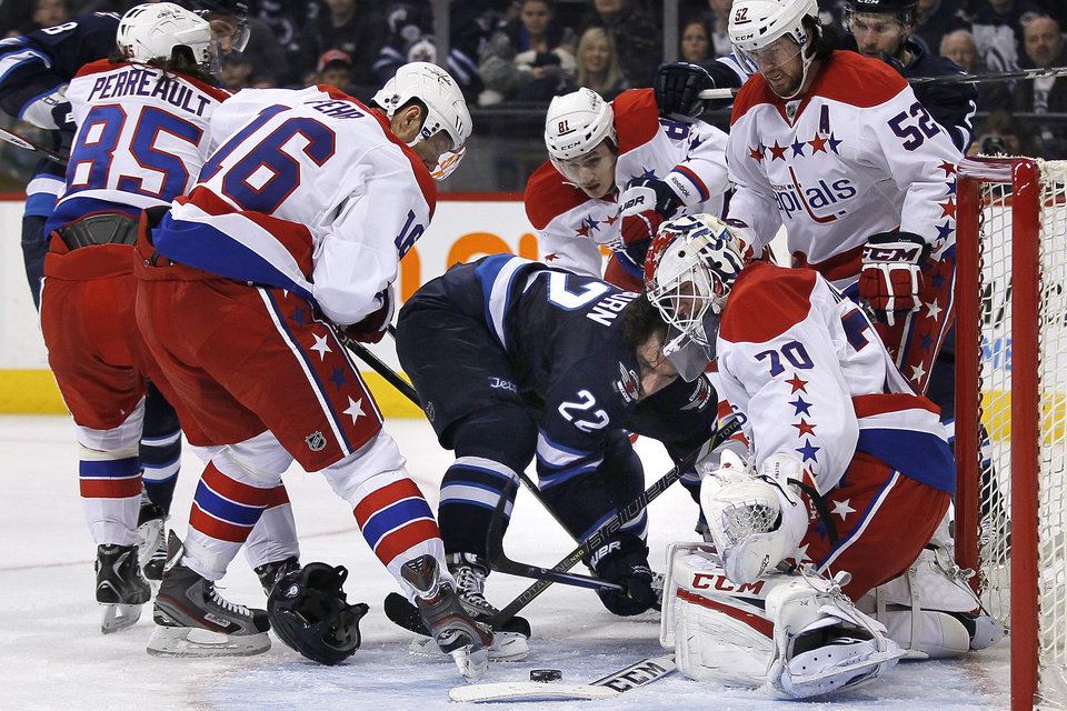 Winnipeg Jets\' Chris Thorburn (22) loses his helmet in front of Washington Capitals goaltender Braden Holtby (70) during the second period of an NHL hockey game in Winnipeg, Manitoba, on Thursday, March 21, 2013. (AP Photo/The Canadian Press, John Woods)