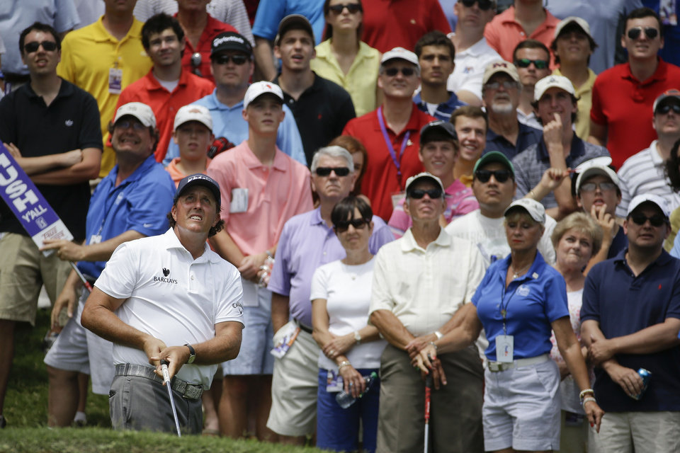 Photo - Phil Mickelson, lower left, watches along with the gallery as his chip shot sails to the green on the 16th hole during the final round of the St. Jude Classic golf tournament Sunday, June 8, 2014, in Memphis, Tenn. Mickelson  made par on the hole and finished the tournament at 6-under 274. (AP Photo/Mark Humphrey)