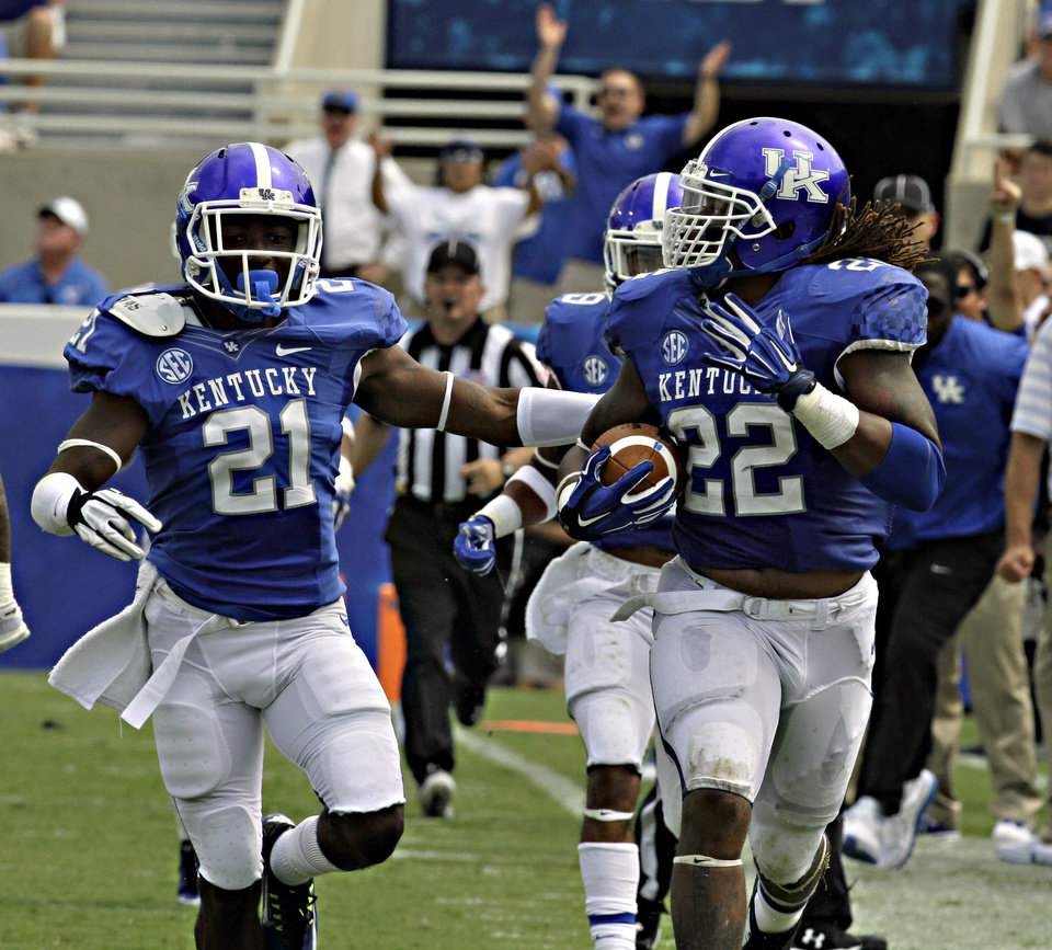 Photo - Kentucky linebacker Khalid Henderson (22) checks over his shoulder after picking up a fumble and running 89 yards for a touchdown against Tennessee-Martin in an NCAA college football game in Lexington, Ky., Saturday, Aug. 30, 2014. At left is teammate Nate Willis (21). Kentucky beat Tennessee-Martin 59-14. (AP Photo/Garry Jones)