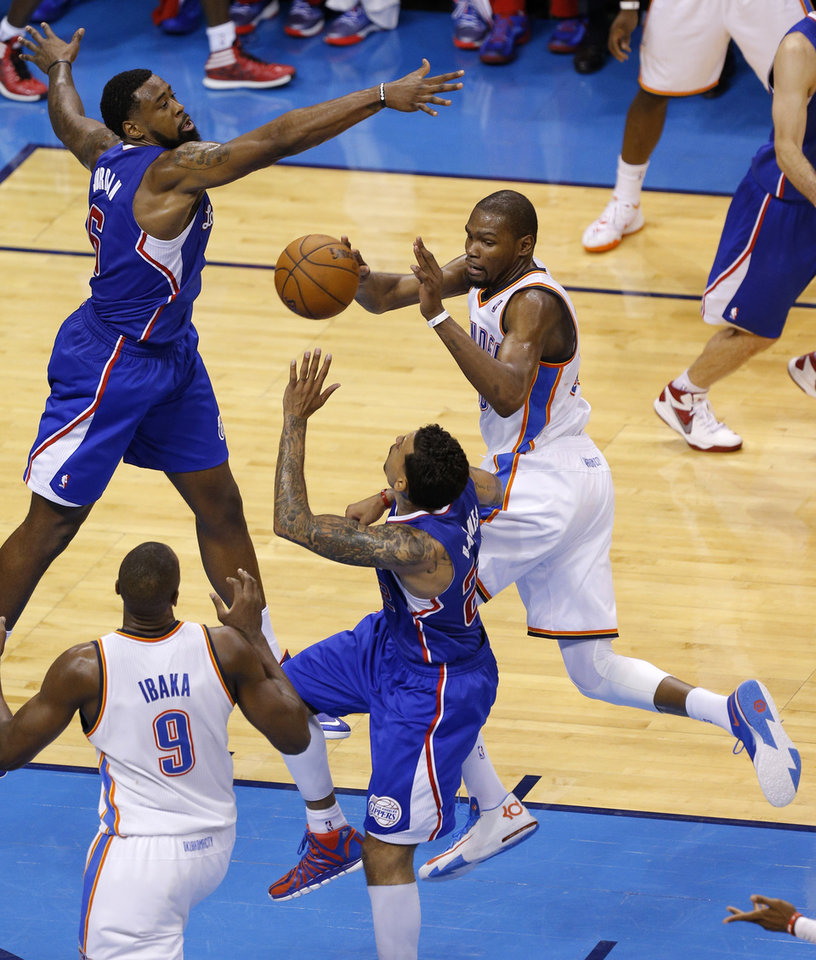 Photo - Oklahoma City's Kevin Durant (35) tries to pass the ball to Serge Ibaka (9) from between Los Angeles' DeAndre Jordan (6) and Matt Barnes (22) during Game 1 of the Western Conference semifinals in the NBA playoffs between the Oklahoma City Thunder and the Los Angeles Clippers at Chesapeake Energy Arena in Oklahoma City, Monday, May 5, 2014. Photo by Bryan Terry, The Oklahoman
