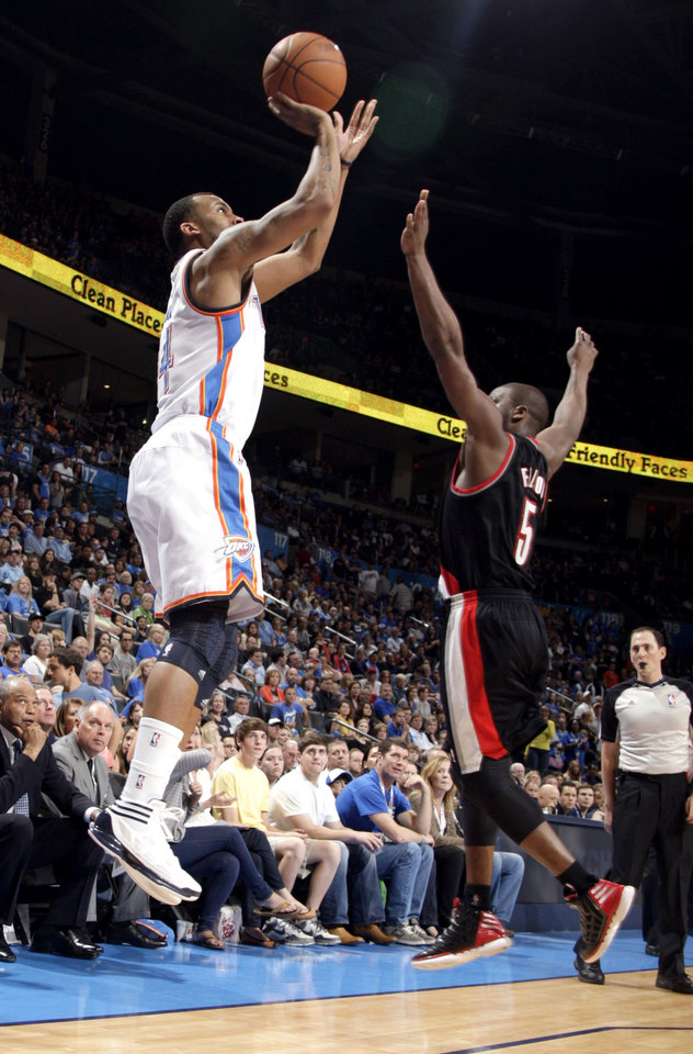 Oklahoma City\'s Daequan Cook (14) shoots a three pointer as Portland \'s Raymond Felton (5) defends during the NBA basketball game between the Oklahoma City Thunder and the Portland Trail Blazers at Chesapeake Energy Arena in Oklahoma City, Sunday, March 18, 2012. Photo by Sarah Phipps, The Oklahoman.