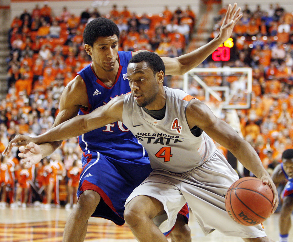 Photo - OSU's Brian Williams (4) drives against KU's Kevin Young (40) in the first half during a men's college basketball game between the Oklahoma State University Cowboys and the University of Kansas Jayhawks at Gallagher-Iba Arena in Stillwater, Okla., Monday, Feb. 27, 2012. Photo by Nate Billings, The Oklahoman