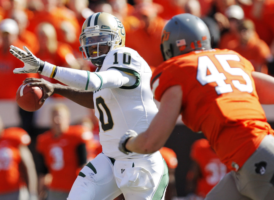 Photo - Baylor's Robert Griffin III (10) passes the ball as Caleb Lavey (45) of OSU defends during a college football game between the Oklahoma State University Cowboys (OSU) and the Baylor University Bears (BU) at Boone Pickens Stadium in Stillwater, Okla., Saturday, Oct. 29, 2011. Photo by Nate Billings, The Oklahoman