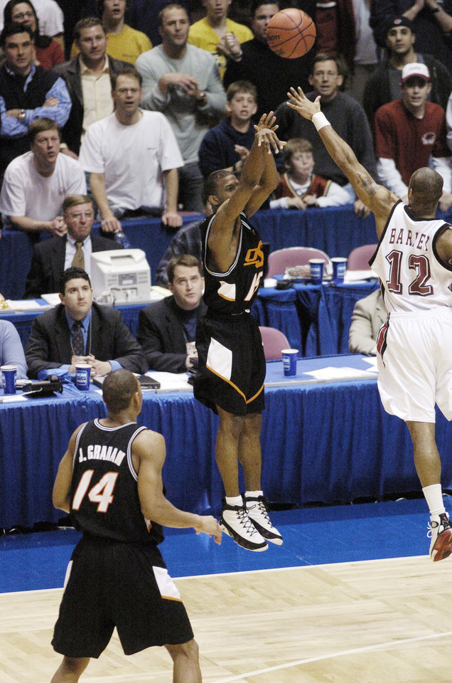 Photo -  OSU's John Lucas puts up the winning 3-pointer over St. Joseph's Tyrone Barley during the East Rutherford Regional Final on March 27, 2004. Photo by Steve Gooch, The Oklahoman Archives   STEVE GOOCH - THE OKLAHOMAN