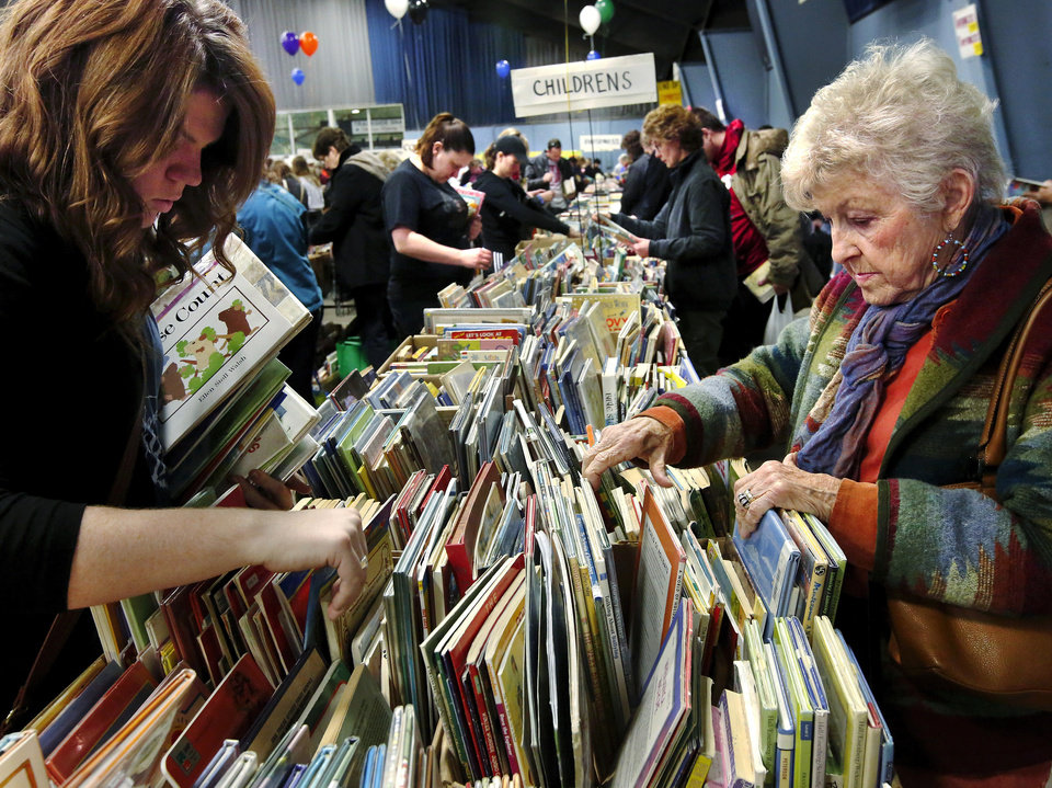 Book sale visitors search through children's books. Several thousand bibliophiles and bargain hunters crowded into Oklahoma Expo Hall at State Fair Park on Saturday, Feb. 23, 2013,  in a quest to find reading material  at deeply discounted  prices.  Friends of the Metropolitan Library System is holding their much-anticipated annual book sale this weekend. The sale continues Sunday from 9 a.m. to 5:30 p.m.   Photo by Jim Beckel, The Oklahoman