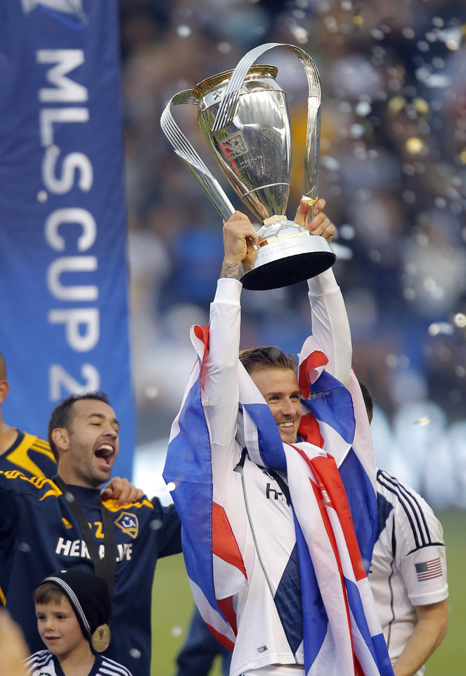 Los Angeles Galaxy's David Beckham, right, of England, holds up the trophy as he celebrates the team's 3-1 win in the MLS Cup championship soccer match against the Houston Dynamo in Carson, Calif., Saturday, Dec. 1, 2012. (AP Photo/Jae C. Hong)