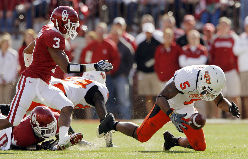 Photo - OSU's Keith Toston (5) recovers the ball after losing it at the end of a run in front of OU's Jonathan Nelson (3) during the first half of the Bedlam college football game between the University of Oklahoma Sooners (OU) and the Oklahoma State University Cowboys (OSU) at the Gaylord Family-Oklahoma Memorial Stadium on Saturday, Nov. 28, 2009, in Norman, Okla.