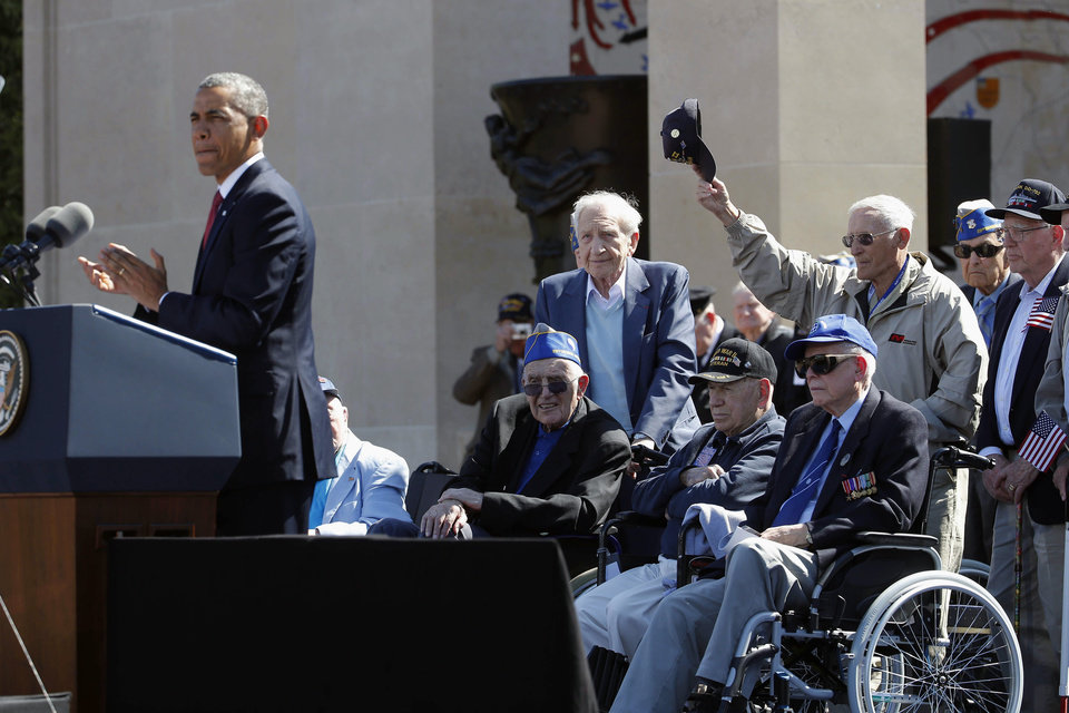 Photo - U.S. President Barack Obama, left, acknowledges veterans as he speaks at the Normandy American Cemetery, at Omaha Beach as he participates in the 70th anniversary of D-Day in Colleville sur Mer in Normandy, France, Friday, June 6, 2014. (AP Photo/Charles Dharapak)